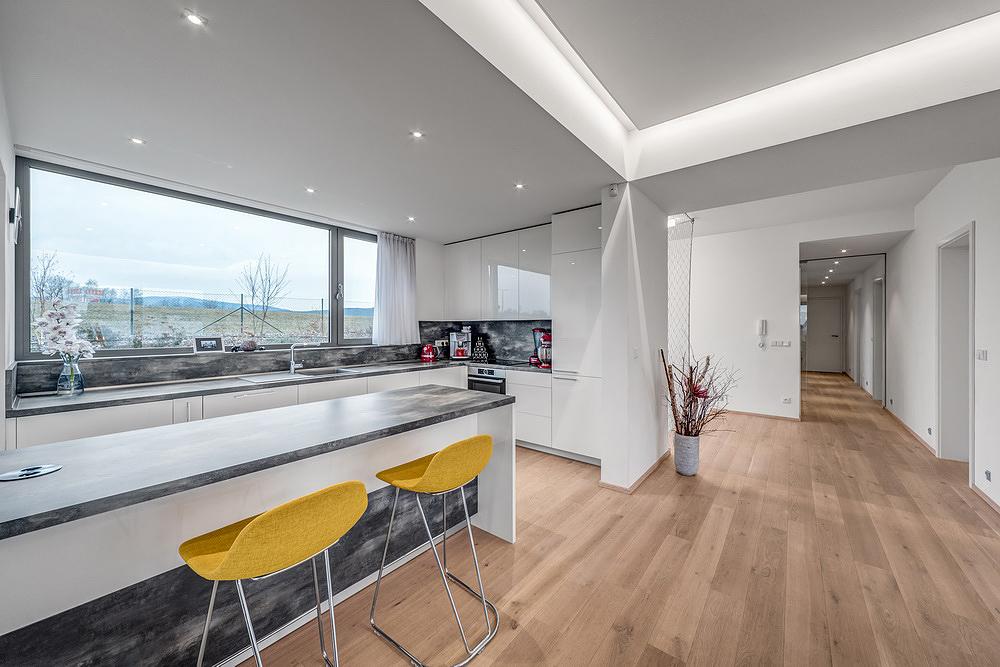 Interiéru dominuje světlé dřevo doplněné bílými a šedými odstíny stěn a nábytku.