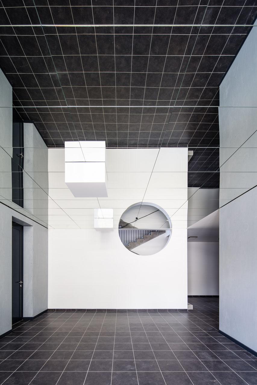 Použití zrcadlového podhledu ve vstupní hale násobí pocit prostoru; celkový dojem umocňuje černobílá barevnost.