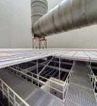 Obr. 12 Pohled na chladicí technologii věže po jejím dokončení, v popředí je možné vidět pochozí lávky umístěné na rozvodné žlaby oteplené vody a ve střední části snímku kompozitní konstrukci eliminátorů a eliminátory samotné