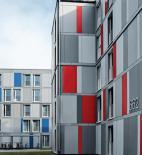 Jednotlivým budovám je přiřazeno primární barevné značení - žluté, modré a červené. Pospolitost venkovní fasády vyjadřují odstupňované šedé tóny - foto © Schüco International KG